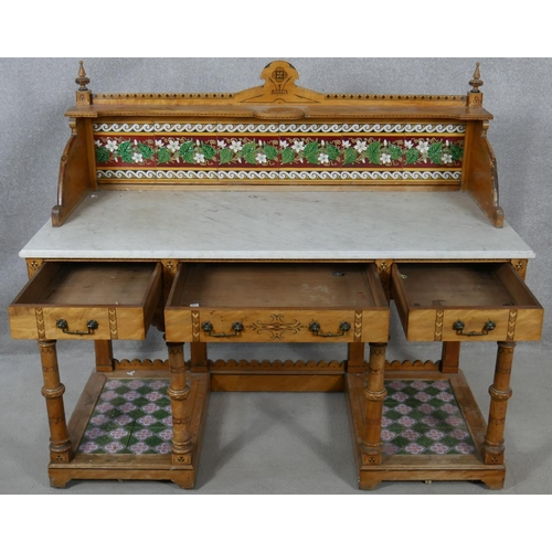 60 - A late 19th century Aesthetic style walnut marble topped washstand with tiled upstand and platform b...