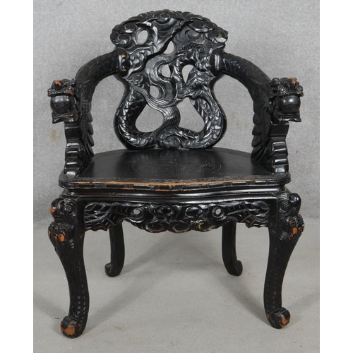 68 - A Chinese ebonised armchair with carved dragon mask arms and panel seat on floral decorated cabriole...