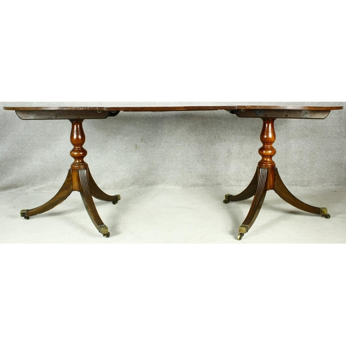 161 - A Georgian style mahogany dining table with extra leaf on twin pedestal reeded swept supports termin...