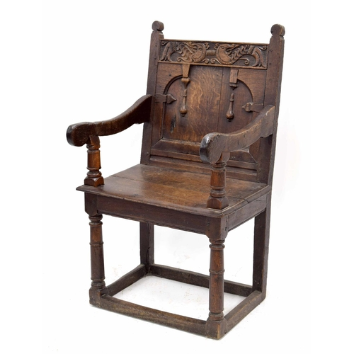 """Mid 17th century oak panel-back open armchair, Yorkshire, circa 1650, the cresting rail carved with mythical beasts over the panelled back and double planked seat, supported upon gun barrel turned circular front legs united by plain stretchers, 25"""" wide, 17"""" deep, 41.5"""" high"""