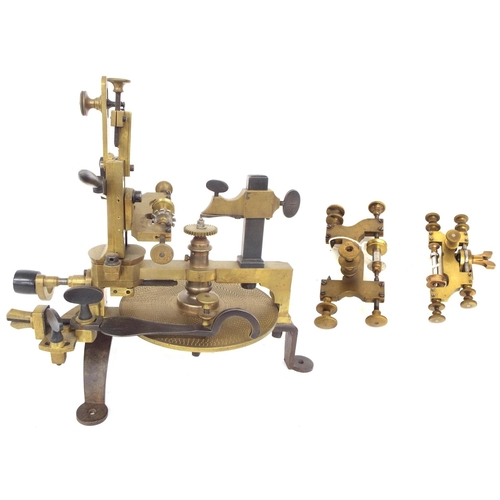 """Interesting and early brass and steel wheel cutting engine with attachments, supported upon cast iron feet, 11.75"""" high overall"""