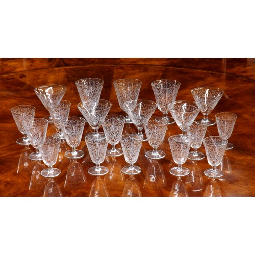 1016 - French suite of drinking glasses with scroll designs,possibly Baccarat comprisingfive champagne co...