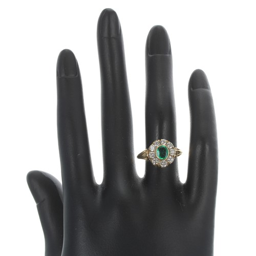 25 - 18ct yellow gold emerald and diamond oval cluster ring, the emerald 0.37ct approx, in a surround of ...