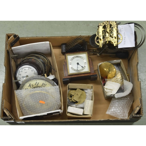 1457 - Cardboard tray containing miscellaneous horological items, including new pendulum bobs, small clocks...