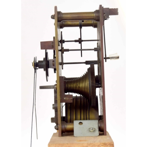 1402 - Single fusee movement with pendulum and hands, mounted upon a wooden block, 9.5