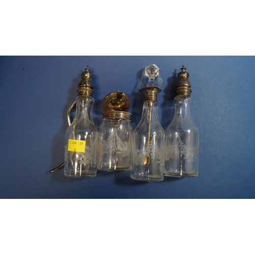 11 - Four Victorian silver mounted condiment bottles; together with a Victorian silver condiment spoon, b...