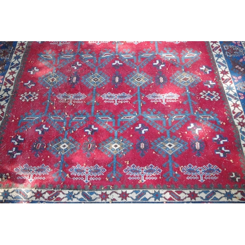 1190 - <strong>A large Persian rug</strong>, having central geometric design with tree motifs on red ground...