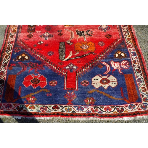 1199 - <strong>A Persian rug,</strong> on blue ground, having central medallion and peacock decoration to c...