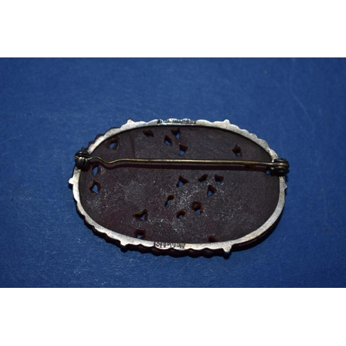 113 - <strong>An Eastern carved carnelian silver mounted brooch,</strong> 5cm....
