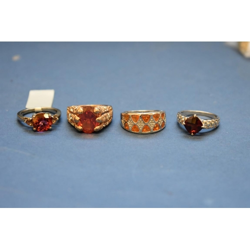 114 - <strong>Four various silver dress rings, </strong>set coloured stones....