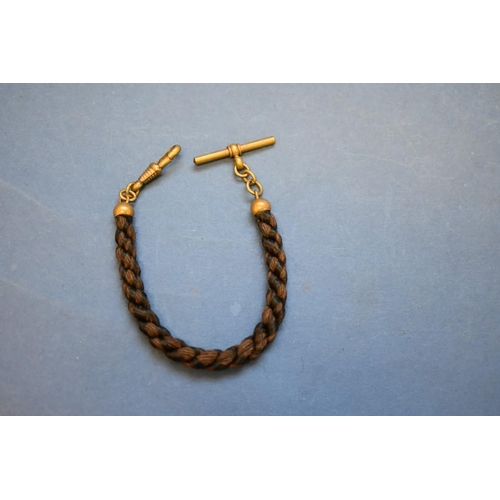 121 - <strong>A memento mori rope twist hair Albert</strong>, having base metal fittings.19cm....