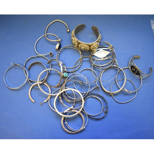 136 - <strong>A quantity of silver and other metal bangles.</strong>...