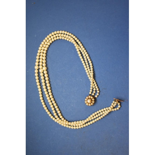 148 - <strong>A three strand graduated pearl necklace,</strong> having 9ct gold and pearl cluster clasp....