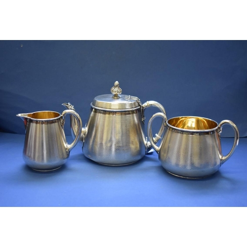 16 - <strong>A Victorian silver engine turned three piece tea set,&nbsp;</strong><em>by John Samuel Hunt,...