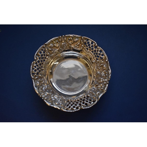 32 - <strong>A foreign metal pierced dish, </strong>14cm; and two metal spoons....