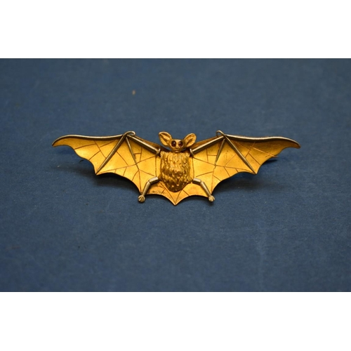 89 - <strong>An unmarked yellow &amp; white gold bat brooch, </strong>having cabochon ruby eyes, 6cm....