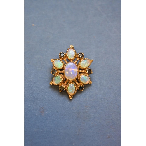 91 - <strong>A 9ct gold star pendant/brooch, </strong>set seven opals and six sapphires, 3cm....