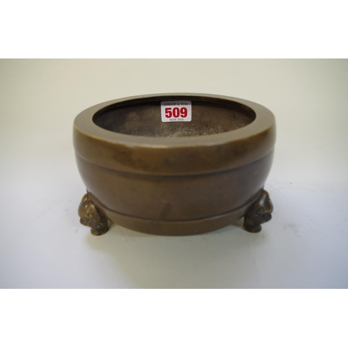 509 - <strong>A Chinese bronze tripod censer,</strong> <em>four character mark,</em> on mask feet, 15cm di...