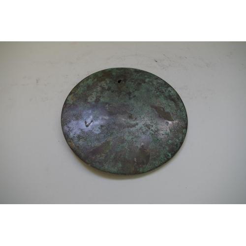 533 - <strong>A Chinese bronze hand mirror,&nbsp;</strong>14cm diameter....