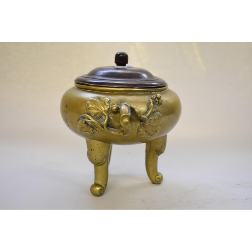 534 - <strong>A bronze twin handled tripod censer,</strong> <em>Qing,</em> with branch form handles and st...
