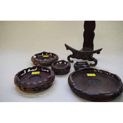 535 - <strong>Six Chinese hardwood stands,&nbsp;</strong>to include: a pair, aperture 10cm; and a plate st...
