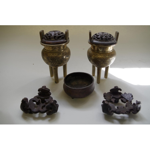 576 - <strong>A pair of Chinese brass twin handled tripod censers,</strong> each with fitted hardwood stan...