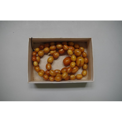 617 - <strong>An amber bead necklace,</strong>of fifty graduated oval beads with further suspended pebble...