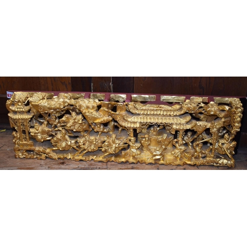 675 - <strong>A Chinese pierced and carved giltwood panel,</strong> decorated with warriors, 20 x 73.5cm....