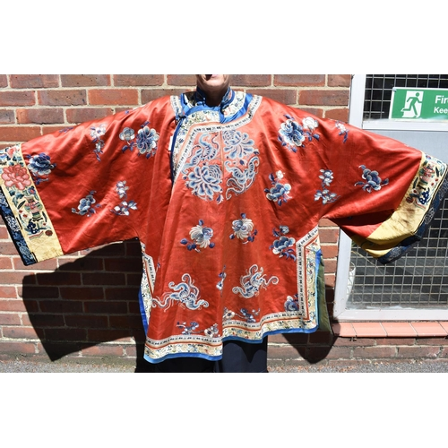665 - <strong>A Chinese embroidered red silk robe.</strong>...