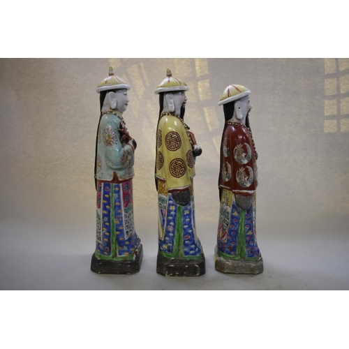 640 - <strong>A set of three Chinese famille rose figures of officials</strong>,&nbsp;<em>late 19th/early ...