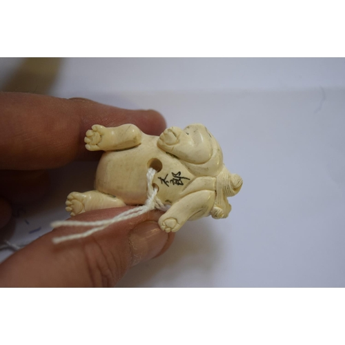 611 - <strong>A Japanese carved ivory netsuke of a qilin</strong>,&nbsp;<em>signed,&nbsp;</em>5cm long....