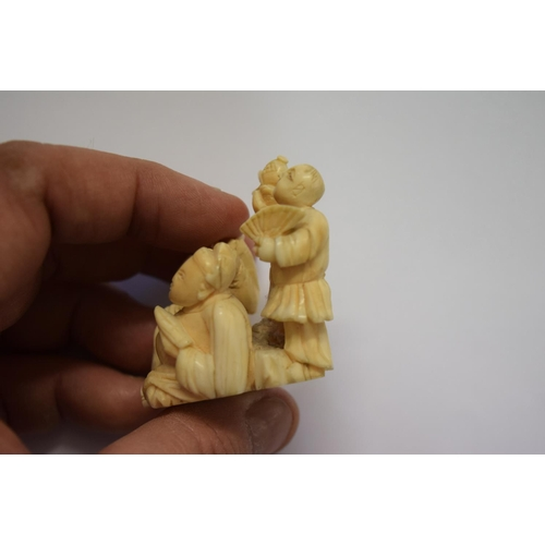 560 - <strong>A Japanese carved ivory okimono figure group</strong>, <em>Meiji period, </em>signed, 6cm wi...