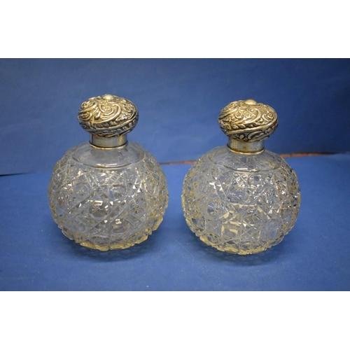 29 - A pair of Victorian silver topped globular cut glass perfume flasks,by Henry Matthews,Birmingham 1...