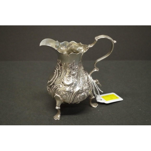 7 - <strong>An ornate silver baluster cream jug,</strong> indistinct marks, 12cm, 149.5g....