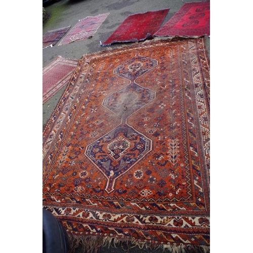 1045 - <strong>A Persian carpet,</strong> having three medallions and floral decoration to central fie...