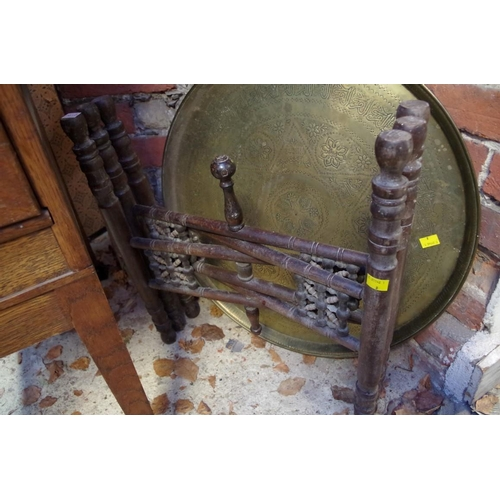 1052 - <strong>An Eastern brass circular tray and folding wood stand, </strong>57.5cm diameter....