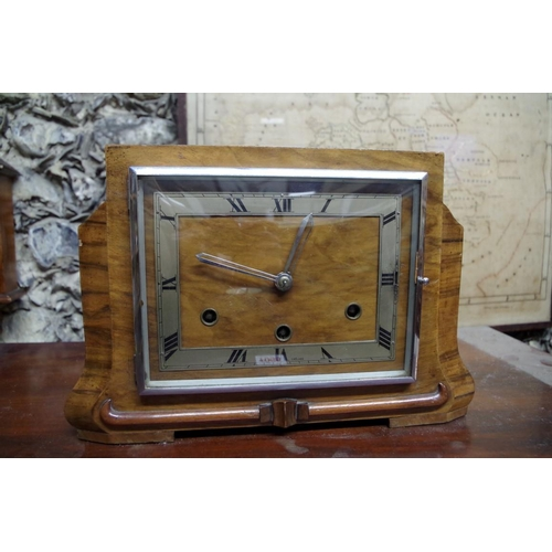 1065 - <strong>An Art Deco walnut mantel clock,</strong> striking on four straight gongs, 33cm wide. ...
