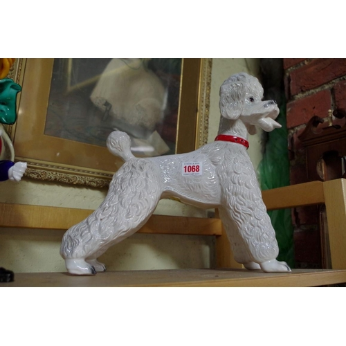 1068 - <strong>A Dutch pottery poodle,</strong>31cm high; together with a Murano glass clown, 33cm hi...