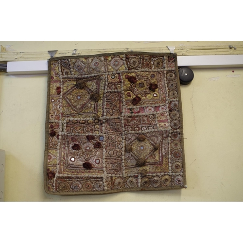 1047 - <strong>An embroidered textile panel,</strong> with mirror and button decoration; together with a si...