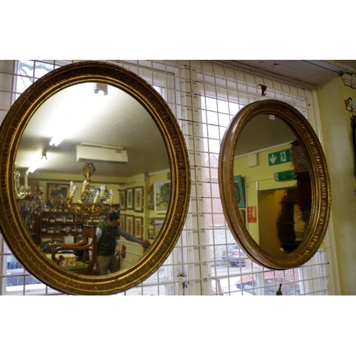1621 - <strong>A pair of gilt gesso framed oval wall mirrors,</strong>61 x 52cm....