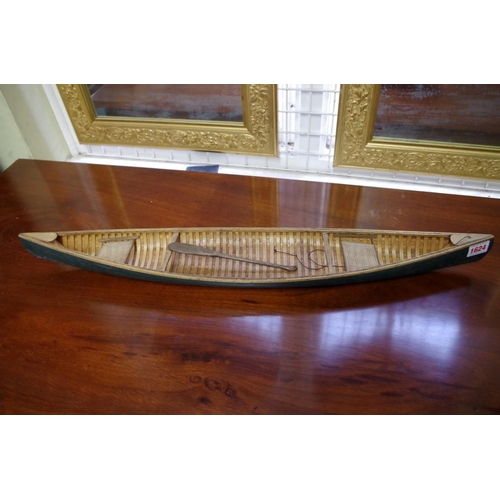 1624 - <strong>A scratch built model of a canoe, </strong>with carvel planking, 70cm long, with small paddl...