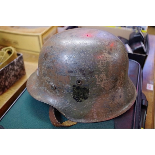 1695 - <strong>A German camouflage helmet,</strong>with Kriegsmarine transfer....