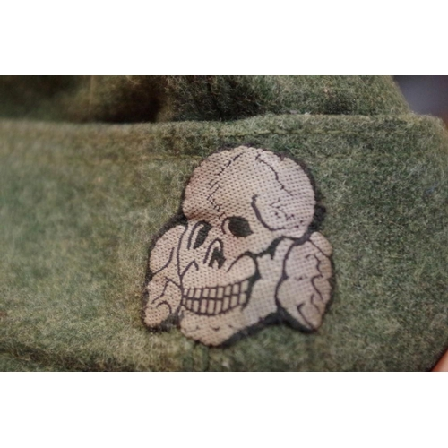 1697 - <strong>A German World War II green felt side cap, </strong>with cloth SS badge. ...
