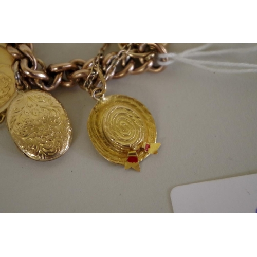 95 - <strong>A 9ct gold chain having twelve charms attached</strong>, including a gold sovereign; one mar...