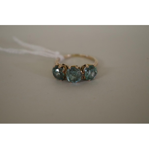 97 - <strong>An unmarked yellow metal three stone aquamarine ring.</strong>...
