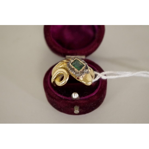 98 - <strong>An unmarked yellow metal coiled snake ring</strong>, the head set Georgian emerald and diamo...
