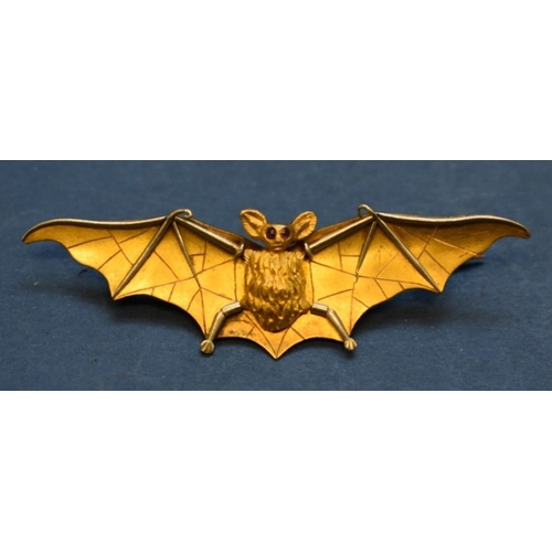 89 - <strong>An unmarked yellow & white gold bat brooch, </strong>having cabochon ruby eyes, 6cm....