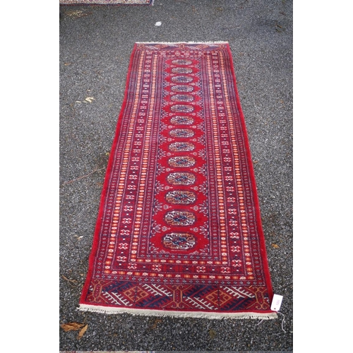 1204 - <strong>A Bokhara style runner, </strong>on a red ground with geometric borders, 210 x 80cm....