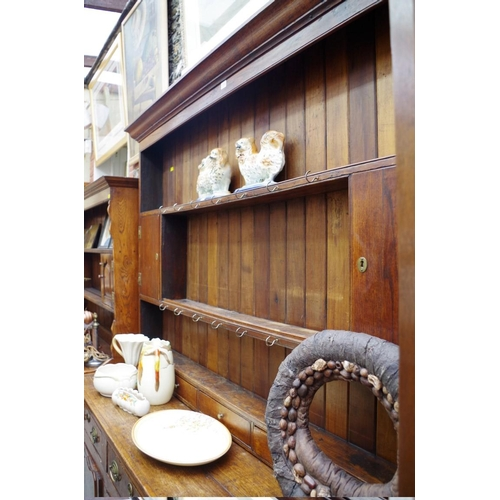1215 - <strong>A George III oak dresser,</strong> the rack back with later back boards, 179.5cm wide....