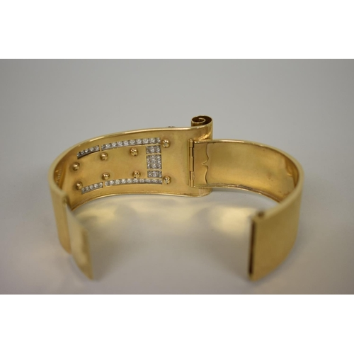 287 - <strong>A stylish diamond set and textured yellow metal hinged </strong><strong>bangle,</strong> unm...